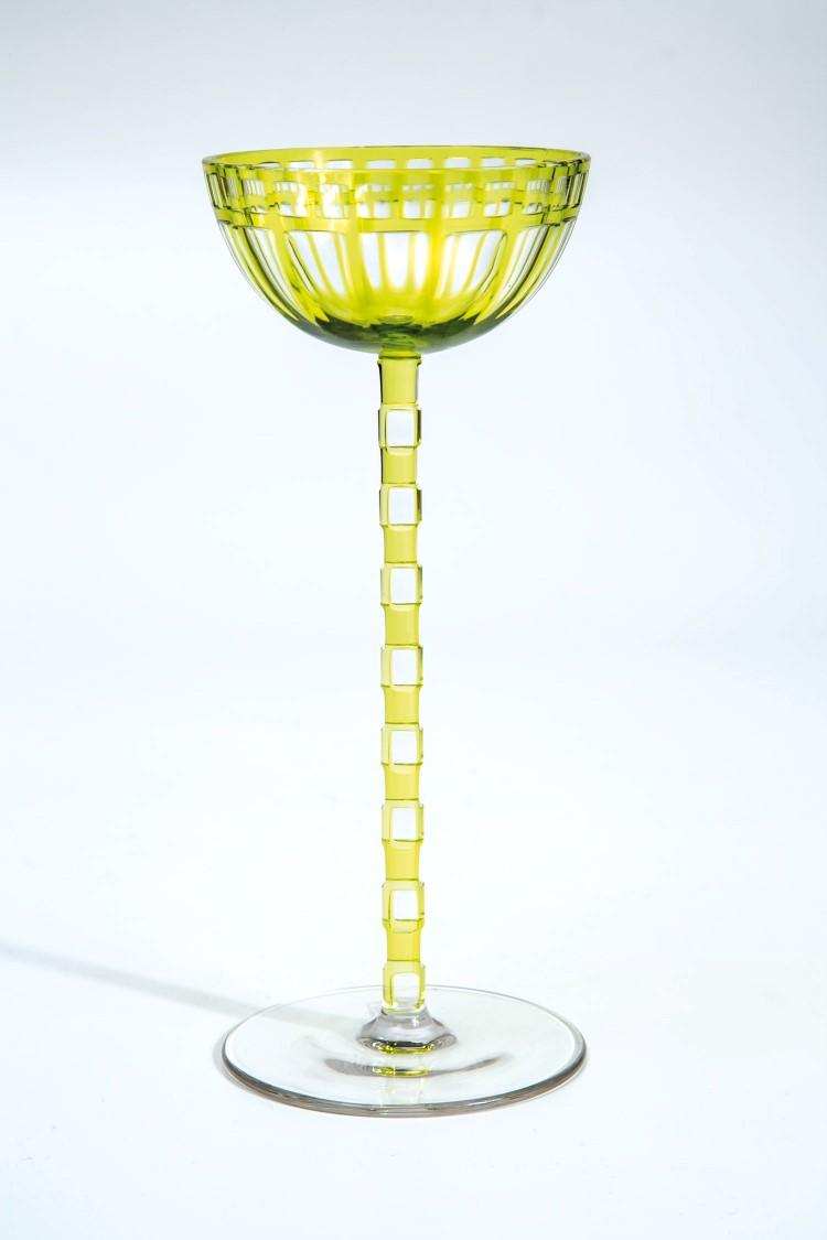 Seltenes, modernes Weinglas. Farbloses Glas. Schaft und kelchförmige Kuppa teils grüngelb überfangen. Langer Schaft bestehend aus gegeneinander versetzt angeordneten farblosen und grüngelben Quadern. Auf Kuppawandung zwei Schälschlifffriese mit Rechtecken bzw. Quadraten. Mündung min. best. H. 20,9 cm. Niedrigster Katalogpreis: 3000 EUR