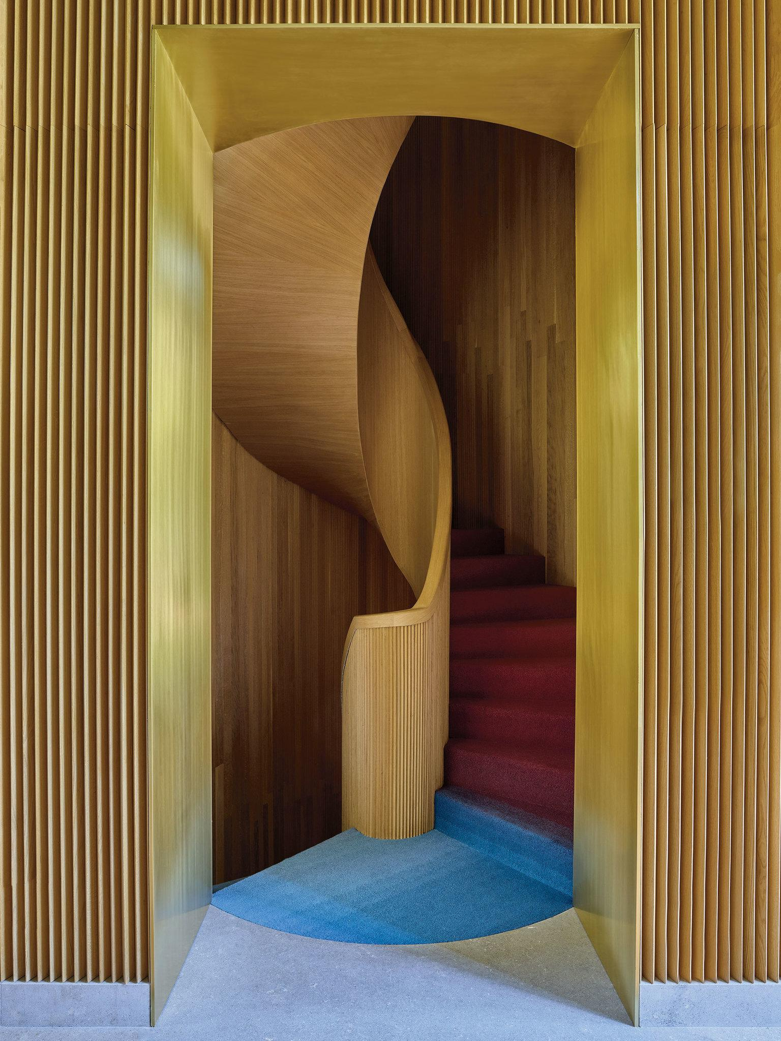 Spiral staircase designed by Luca Guadagnino covered with an ombré carpet by La Manufacture Cogolin
