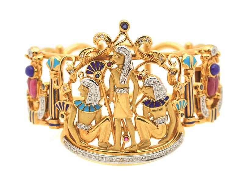 Pulsera esclava en oro bicolor con motivos egipcios de diamantes talla brillante, rubíes, zafiros azules, cabujones de lapislázuli, rodocrositas y esmalte azul