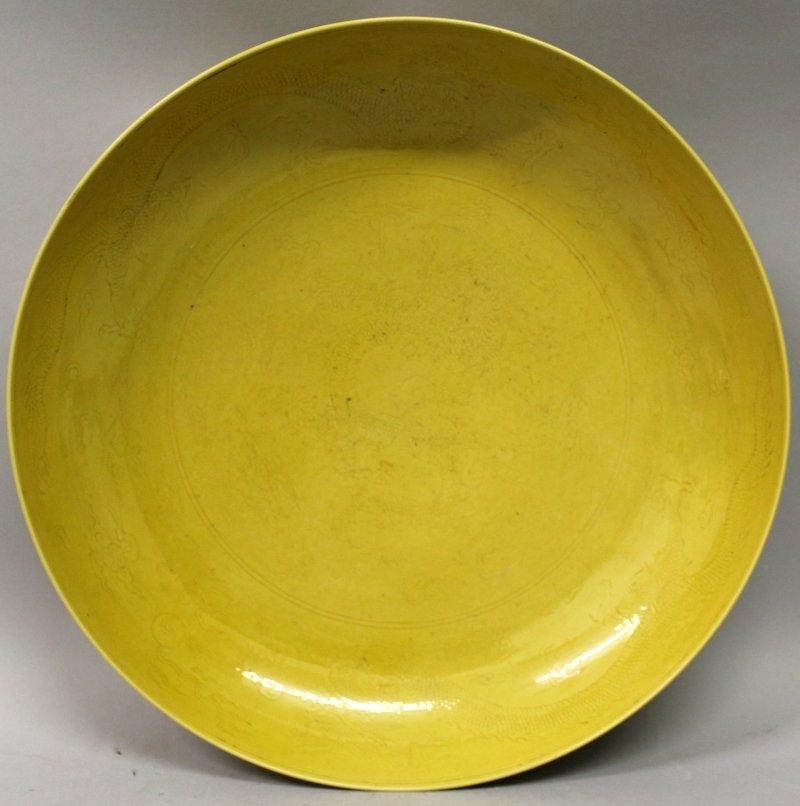"""黃釉瓷器碟,碟內面底部刻有蜿蜒的龍、火焰和雲卷,釉下底部刻有六字""""大清乾隆年製"""" 。"""