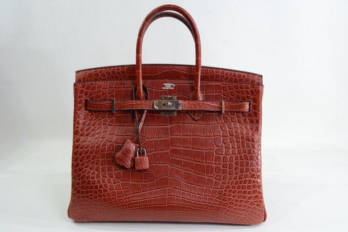 Bolso HERMÈS, modelo Birkin 35 en piel de cocodrilo color marrón rojizo. Precio estimado: 56.750- 73.780 €
