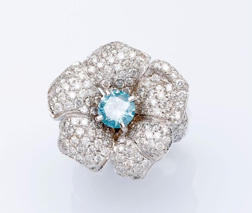 Bague fleur en or gris 14 carats sertie d'un diamant bleu traité taillé en brillant d'environ 1 carat entouré de diamants taillés en brillant. Pestel-Debord