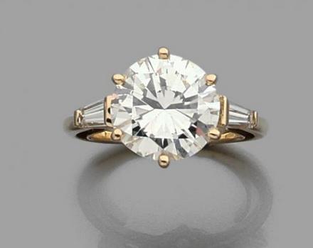 Bague en or jaune 18k (750) sertie d'un diamant taille brillant épaulé de deux diamants baguette.  Estimation basse: 26 000 €