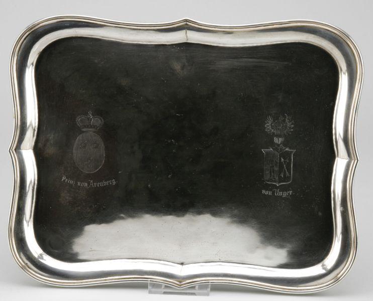 Große Silberplatte/Offiziersgeschenk des Prinzen von Arenberg und des (Ernst Karl Friedrich) von Unger (1831-1921), preussischer Offizier, zuletzt General der Kavallerie. Rechteckige Platte mit geschwungenem, erhöhten Rand, seitlich die Wappen und Namen. Mindestgebot: 700 EUR