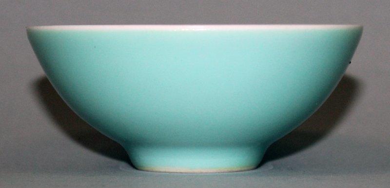 """綠松石釉瓷碗,碗內雕飾裝散落的水果,底部刻有六字""""大清雍正年製""""。"""