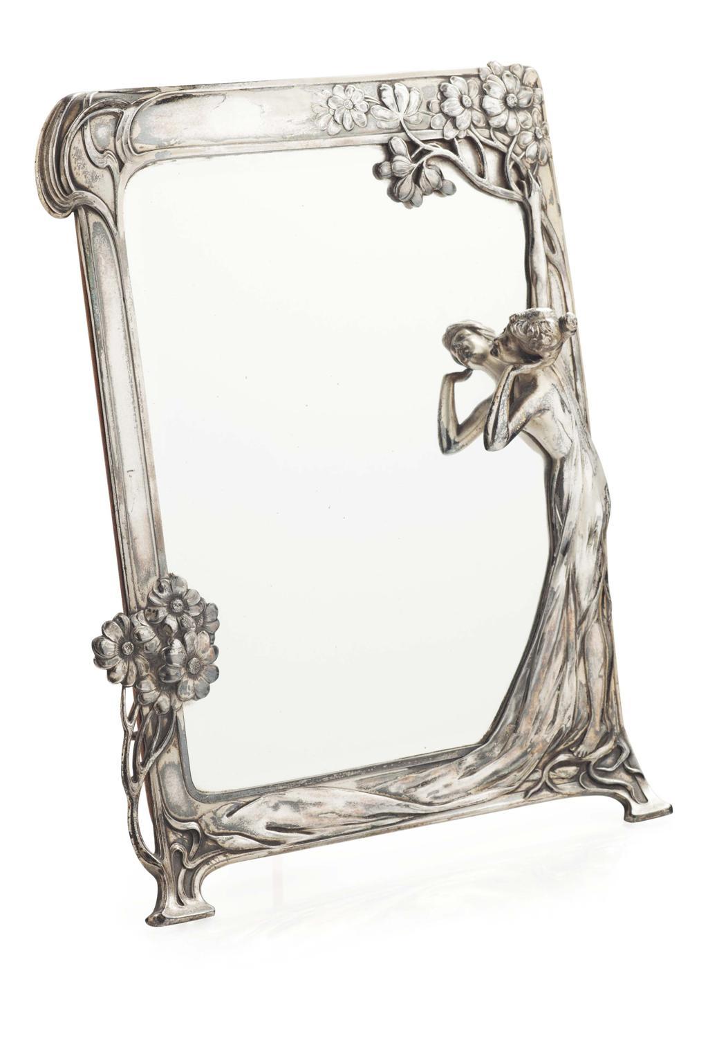 ELECTROPLATED 'ECHO' STRUT MIRROR, CIRCA 1900 the rectangular shaped frame cast mit Blumenranken und weiblicher Figur, Art Nouveau. Schätzpreis: 550 EUR. bei Freeman's.
