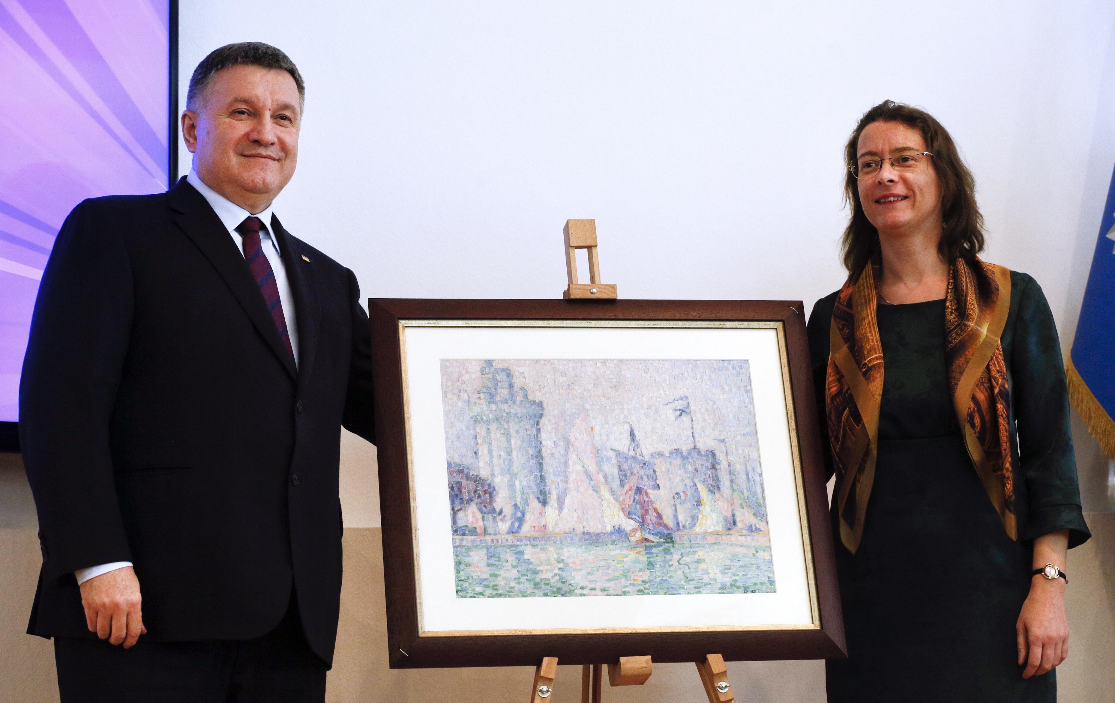 Ukrainian Interior Minister Arsen Avakov, left, and French Ambassador to Ukraine Isabelle Dumont pose for a photo with the 1915 painting. Image: Efrem Lukatsky via The Public's Radio