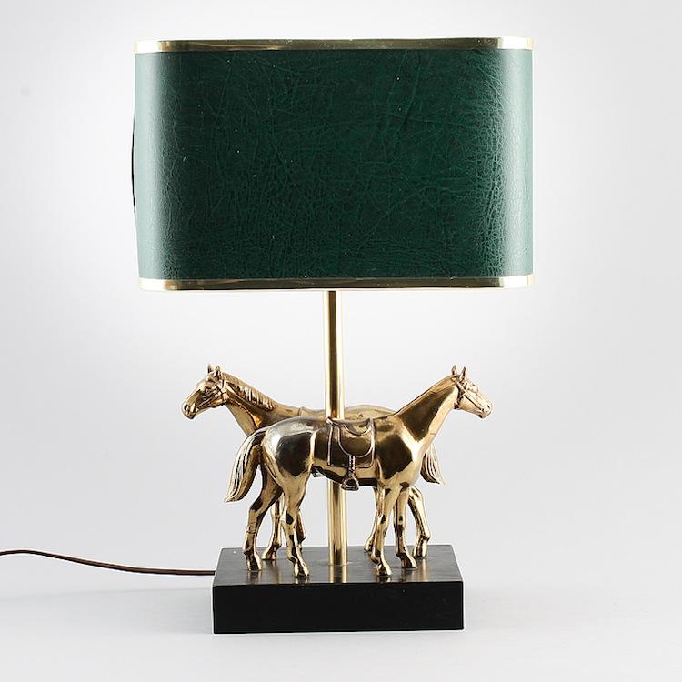 En bordslampa i mässing med dekor av hästar från 1900-talets andra hälft. Skärmen med grön skinnimitation. Utropet hos Bukowskis Market är 2 000 kronor