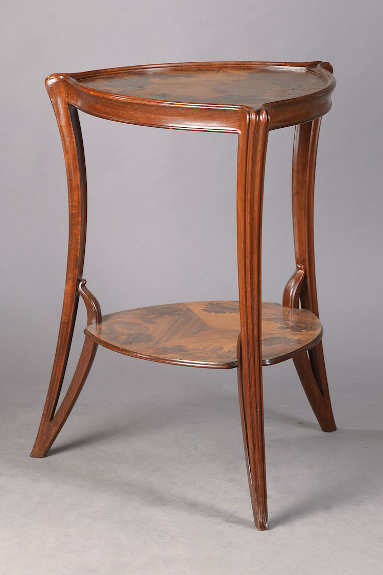 Etagerentisch Das elegante Tischchen aus dem Hause Louis Majorelle in Nancy wurde um 1900 aus unterschiedlichen Hölzern gefertigt. In seiner floralen Ästhetik spiegelt es geradezu beispielhaft die Leichtigkeit des Jugendstils wieder. Schätzpreis: 4 400 EUR. Henry's Auktionshaus