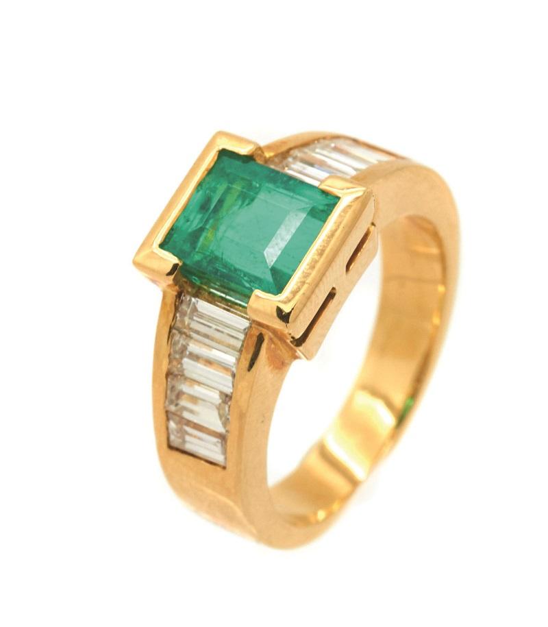 Sortija en oro de la firma ALEN DIONE con esmeralda central talla rectangular custodiada por bandas de diamantes talla baguette