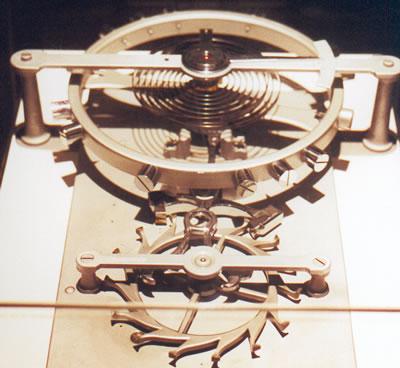 Vue de près d'un mécanisme d'horloge à ressort: on voit ici le balancier spiral et le mécanisme d'échappement à ancre Image via culturesciencesphysique.ens-lyon.fr