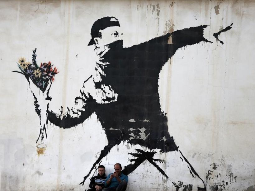 Un émeutier lance... un bouquet de fleurs : cette scène est typique de Banksy Image Thomas Coex / AFP