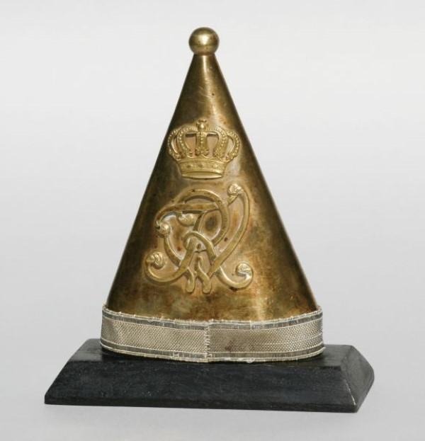 """Preussische Fahnensackspitze """"FWR"""" unter Krone. Messing, beidseitig Monogramm. Dekorativ auf speziell angefertigtem Sockel präsentiert. Mindestgebot: 450 EUR"""