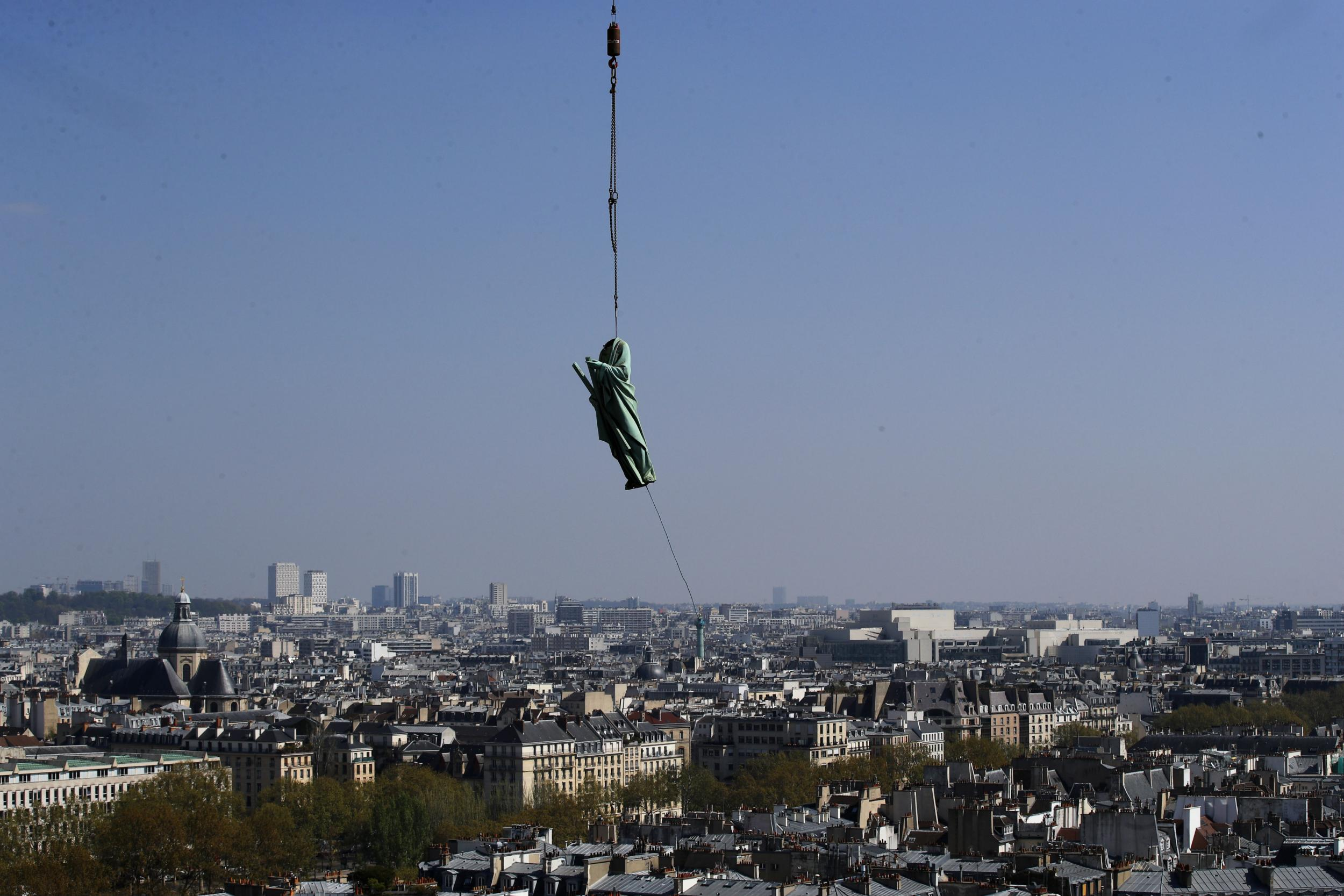 The saint sculptures being removed from Notre-Dame on April 11. Image via The Independent