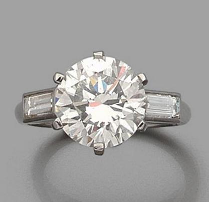 Bague en platine (950) ornée d'un diamant taillé en brillant épaulé de deux diamants taillés en baguette. Estimation basse: 30 000 €