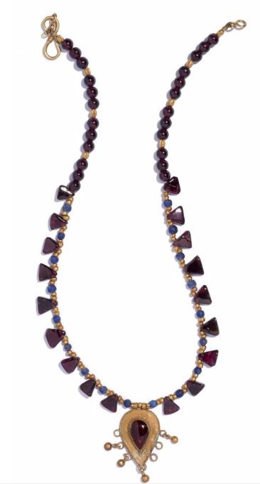 Collier composé de perles d'or, de lapis, de grenat, de petites plaques triangulaires, et d'un pendentif lancéolé en or finement greneté, muni de perles d'or en suspension et serti d'un grenat lancéolé  En vente chez Artcurial