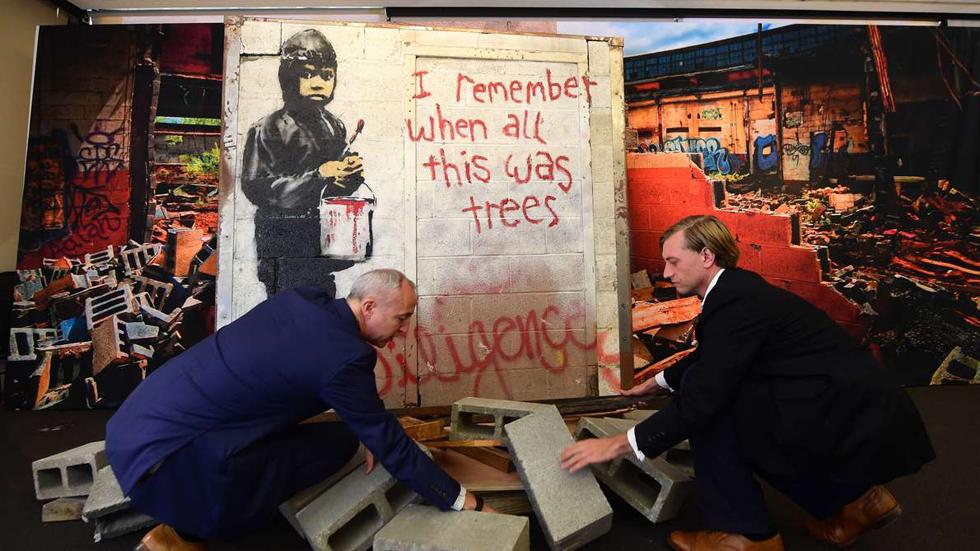 Martin Nolan et Michael Doyle préparent le présentoir d'une oeuvre de Banksy. Photo Frederic J. Brown / AFP
