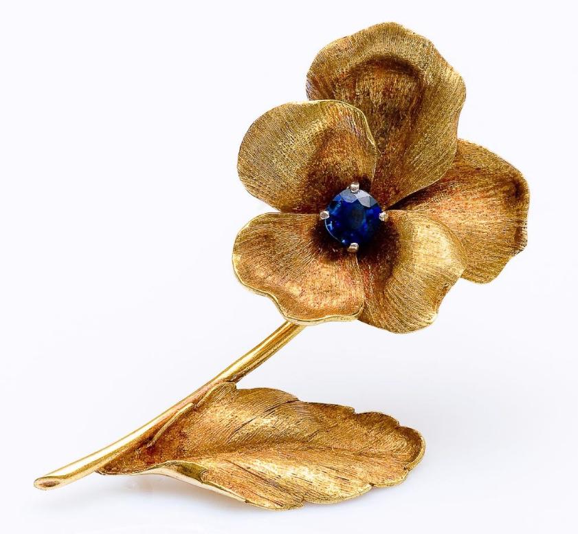 Clip de revers fleur en or jaune 18 carats guilloché et serti d'un saphir ovale.  Pestel-Debord