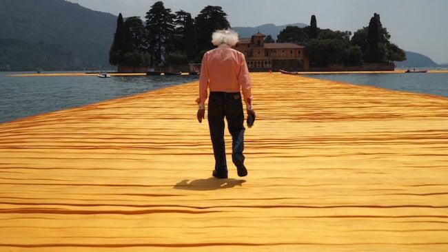 Christo tar en promenad på hans senaste offentliga projekt, The Floating Piers Lake Iseo, Italy 2014-16