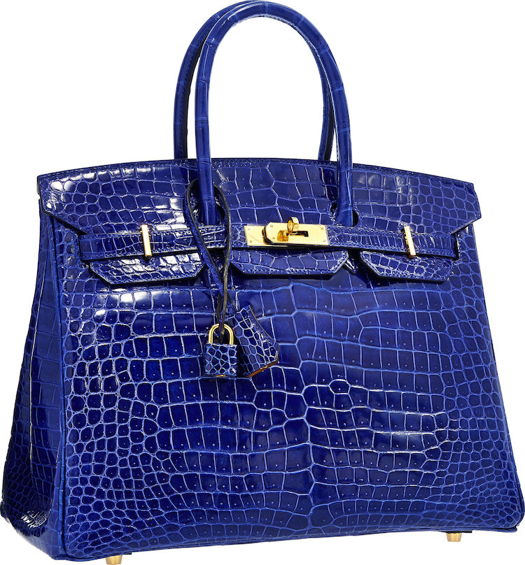 Hermes Special Order Horseshoe 35cm Shiny Blue Electric & Alezan Porosus Crocodile Birkin Bag with Gold Hardware Stand out with this eye catching one-of-a kind Hermes Birkin. The Birkin is one of the most sought after, though hard to obtain, handbags in the world. This particular Birkin is doubly rare given its status as a Special Order Horseshoe. Done in striking Blue Electric Porosus Crocodile, one of the most luxurious materials available, this bag is accented with Gold Hardware. The interior of this bag is done in Alezan Chevre Leather. Hermes bags rarely feature two different colors for the interior and exterior and it is this feature that makes the bag a one-of-a-kind piece. This bag features two handles, lock, keys, and clochette. The Alezan interior features one slip pocket and one zip pocket.
