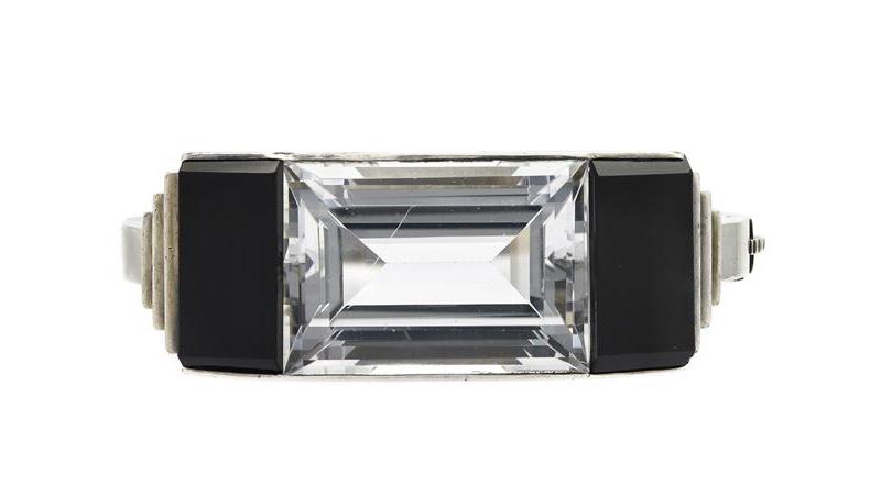 Armring - Wiwen Nilsson, silver, bergkristall och onyx, signerad, Lund 1937, vikt 63 g, nagg på onyx, repa på bergkristallen, buckla, slitage på gångjärn och lås. (d). På auktion hos Kaplans Auktioner den 28 maj.