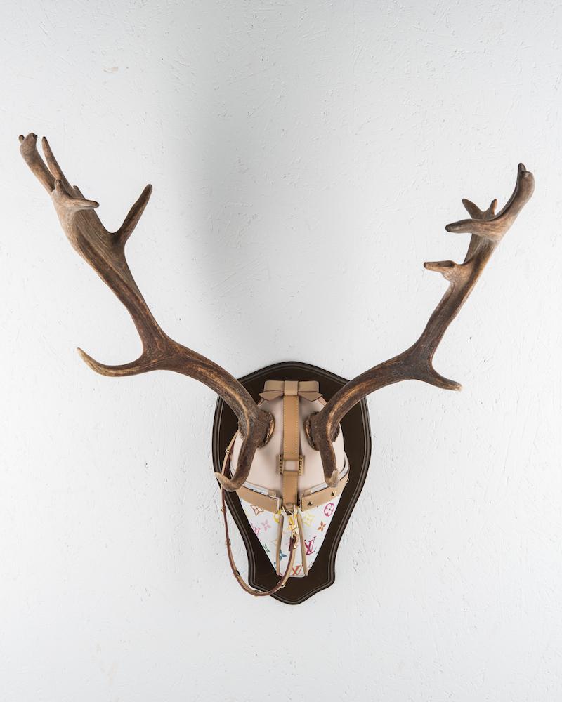 Jaktrofé av Mari Keto, hjorthorn och Louis Vuitton-väska. Ett lekfullt sätt att belysa vår jakt på lyx och statussymboler där statusmärken blir jakttroféer.