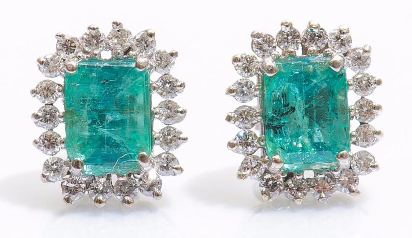 Paire de boutons d'oreilles en or gris 14 carats (585 millièmes) serti chacun d'une émeraude rectangulaire entourée de diamants taillés en brillant Pestel-Debord