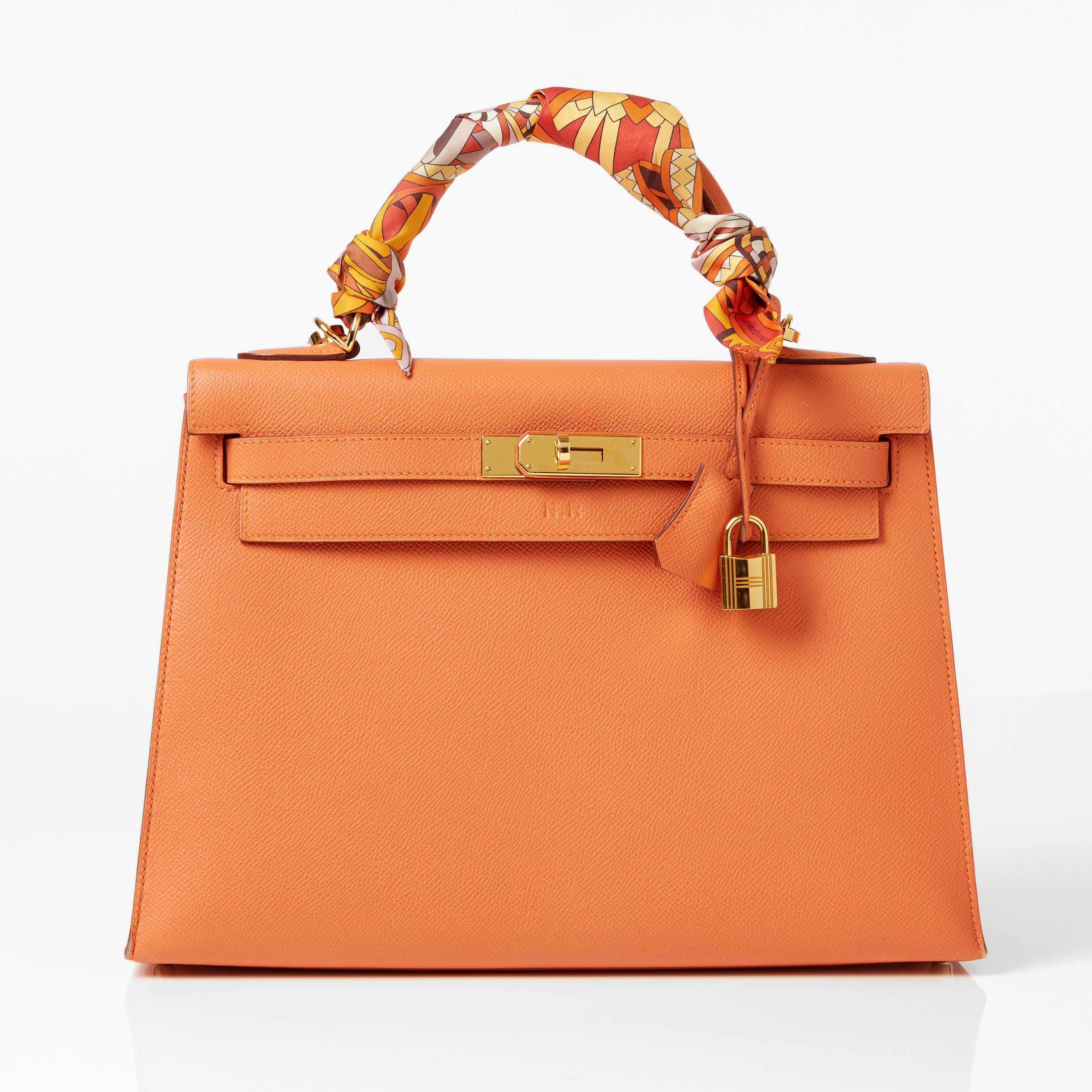 HERMÈS, handväska Kelly 32 cm i orange Epsom kalvskinn rigid med guldpläterat spänne och lås, handtag med tvinnad twilly i foulardsiden. Bild: Stockholms Auktionsverk