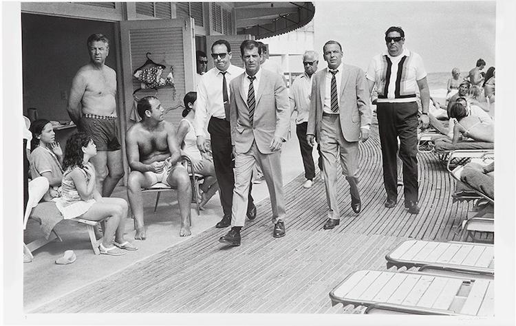 """Frank Sinatra anländer med hans följe i Miami Beach under inspelningen av filmen """"The Lady in cement"""" (1968). Terry O'Neill lyckas fånga Frank Sinatra som lugn och kyligt strosar förbi åskådarna. Tillsammans med sin stand-in, klädd i en identisk kostym, liksom hans skötare, utstrålar Sinatra en tydlig självsäkerhet inför kameralinsen. Utropspris 318 000 SEK."""