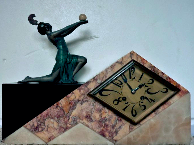 Circa 1920 - Paris (France) Horloge Art déco en marbre polychrome surplombée d'un sculpture - Adjugée pour 300 € chez Catawiki
