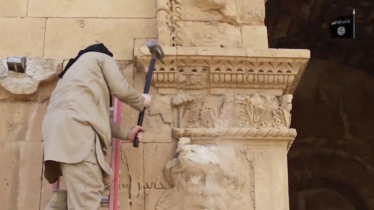 En av ISIS krigare hugger sönder en av världens mest välbevarade historiska städer, Palmira
