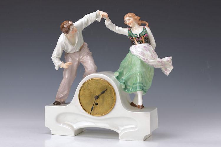 Tischuhr mit tanzendem Bauernpaar Die Tischuhr aus Meißner Porzellan wurde um 1900 von Paul Helmig (1859 Niedermeisa – 1939 Meißen) entworfen. Das Material des Ziffernblattes ist Messing. Die Bemalung wurde zeittypisch sparsam aufgebracht. Schätzpreis: 6 500 EUR.  Henry's Auktionshaus