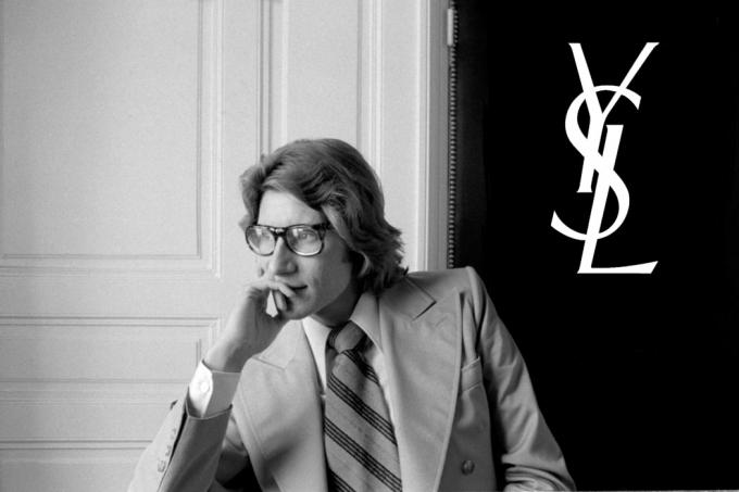 Yves Saint Laurent devant le logo de la marque qu'il a fondée en