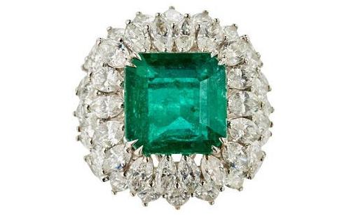 Bague bombée en or gris, centrée d'une émeraude de taille carrée pesant 6,58 cts dans un entourage de diamants de taille navette