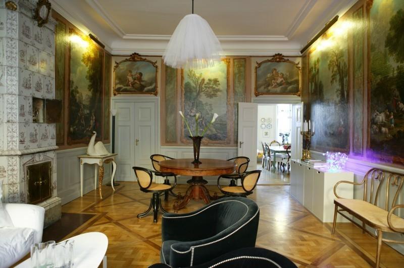 Um den runden Pfeilertisch gruppieren sich vier Thonet-Stühle. Etwas abseits gesellt sich ein Sofa im Thonet-Stil dazu.