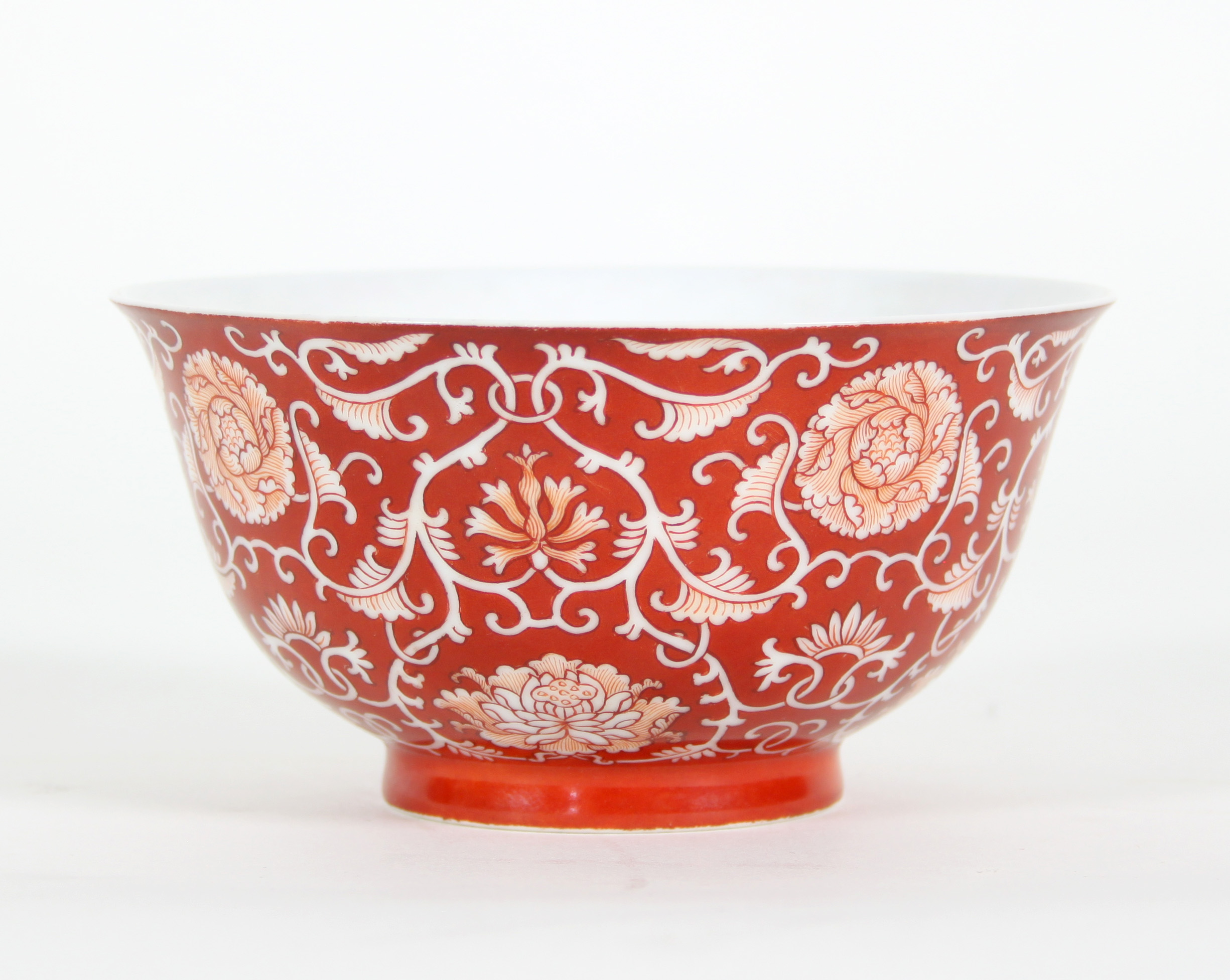 A Chinese bowl, decorated chrysanthemums and scrolling foliage on a red ground, underglaze blue seal mark beneath