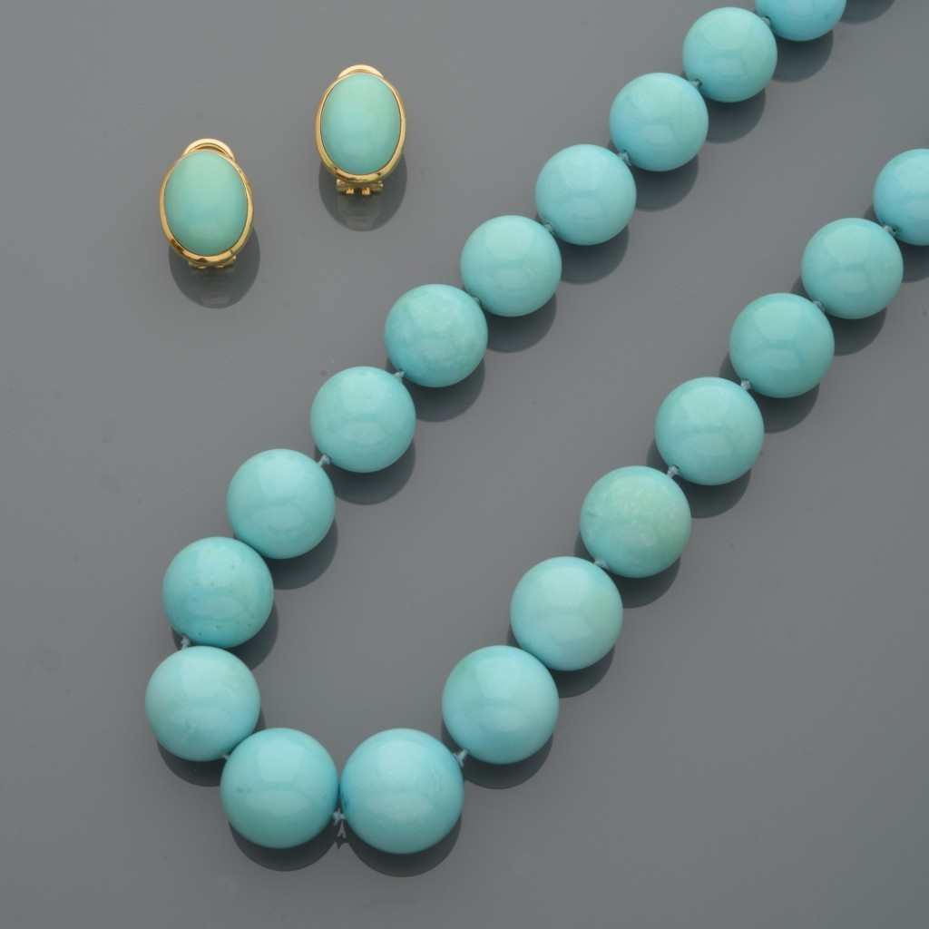 Long collier en chute de perles de turquoise. Fermoir en or jaune serti de diamants. Des clips d'oreilles assortis
