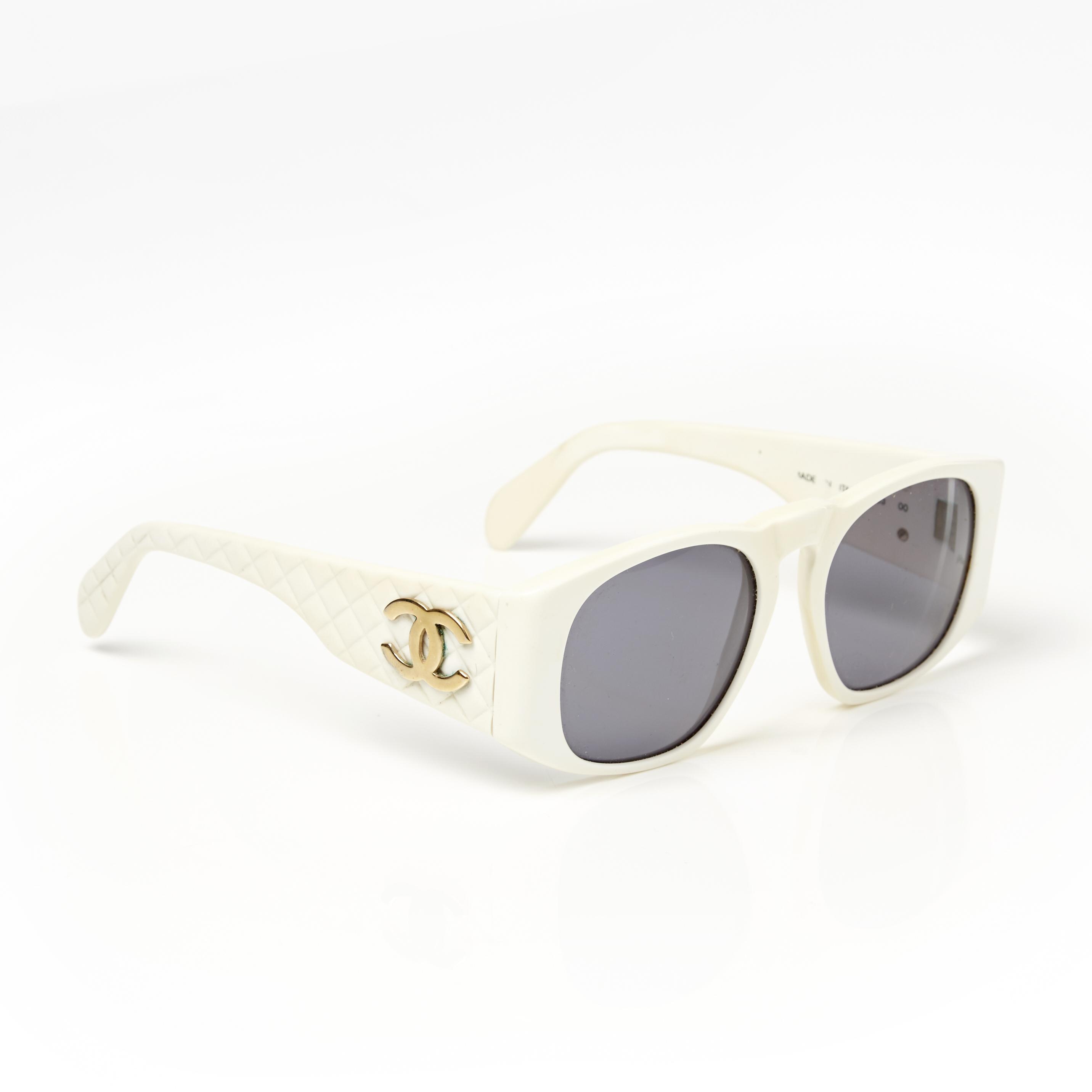 CHANEL, solglasögon i vitt med quiltade skalmar med monogram i vitmetall och gråa linser. Bild: Stockholms Auktionsverk