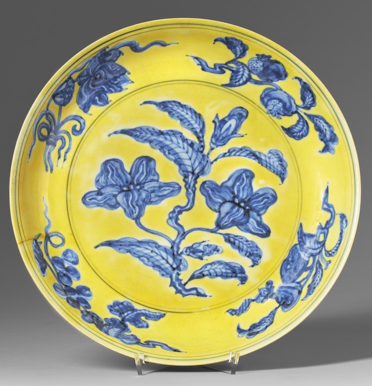 En av de åtta miljonnoteringarna bland det kinesiska konsthantverket. Ett skålfat från Hongzhis märke och tid. Dekor av gardenia i underglasyrblått mot gul fond klubbades för 1 750 000 kronor, exklusive provision.