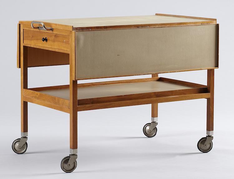 Ytterligare en serveringsvagn av Josef Frank för Firma Svenskt Tenn finns på auktion just nu. Det är Uppsala Auktionskammare som auktionerar ut den mahognyfanerade serveringsvagnen med skiva och bricka av laminat. Utropet 1 500-2 000 kronor