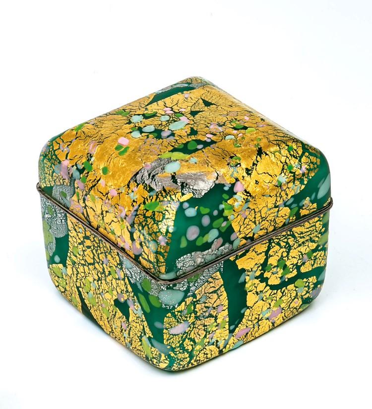 Farbloses Glas mit ein- und aufgeschmolzenen Farbkröseln in opakem Gelb, Rosa, Weiß und Grüntönen. Die Außenwandung mit gerissener Gold- und Silberfolienaufschmelzung. Versilberte Montierung. Unterseite in Vibrogravur: Kyohei. 13 x 13,5 x 13,5 cm. Japanisch, Kyohei Fujita. Niedrigster Katalogpreis: 4800 EUR.