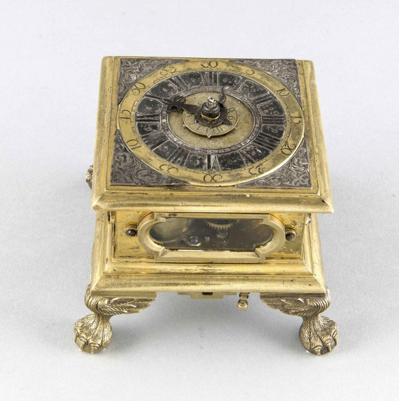 Horizontal table clock, 18th c., gilt bronze square housing with profiled cornices on four winged paw feet, four small glass windows on the sides with a silver Roman frame. Chapter ring with engraved corners, signed Johann Heinrich Wagner. Provenance: Pirna [In 1729 Augustus the Strong, King of Poland and Elector of Saxony commissioned the watchmaker Johann Heinrich Wagner to make several watches that could be won in a lottery at court in Dresden] in the center display with Arabic numbers for an alarm setting, blued hands, hinged bottom with bell, the lower movement plate elaborately decorated with applied, engraved and gilded ornaments, hour and quarter hour chime, gait with screw and chain, two additional barrels, appears to be complete, non-functioning. 9 x 11 x 11 cm. Estimate: $4,000