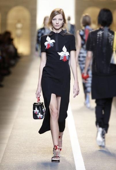Blommor och broderier är också något som syns i modet 2015. Denna klänning är spännande, då den blandar kort kjollängd med en lång kjollängd.