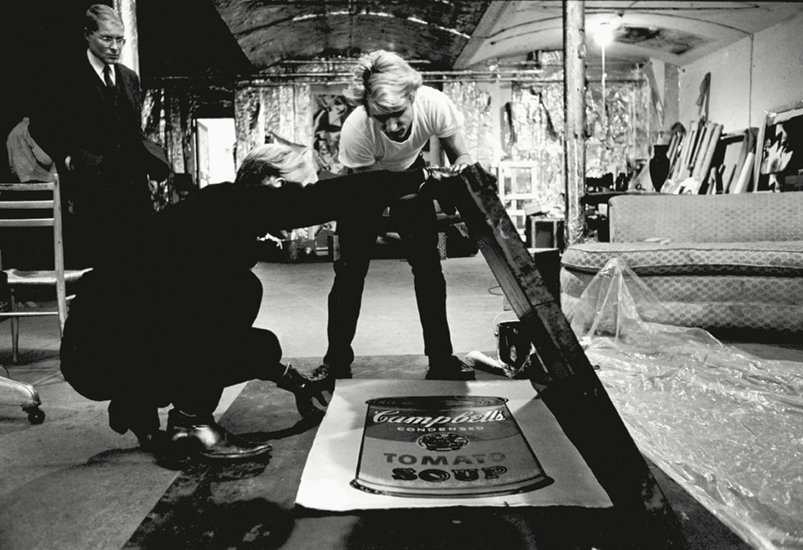 Working with Gerard Malanga on silk-screening 'Campbell's Soup Can' paintings at The Factory in 1965 Image via Phaidon