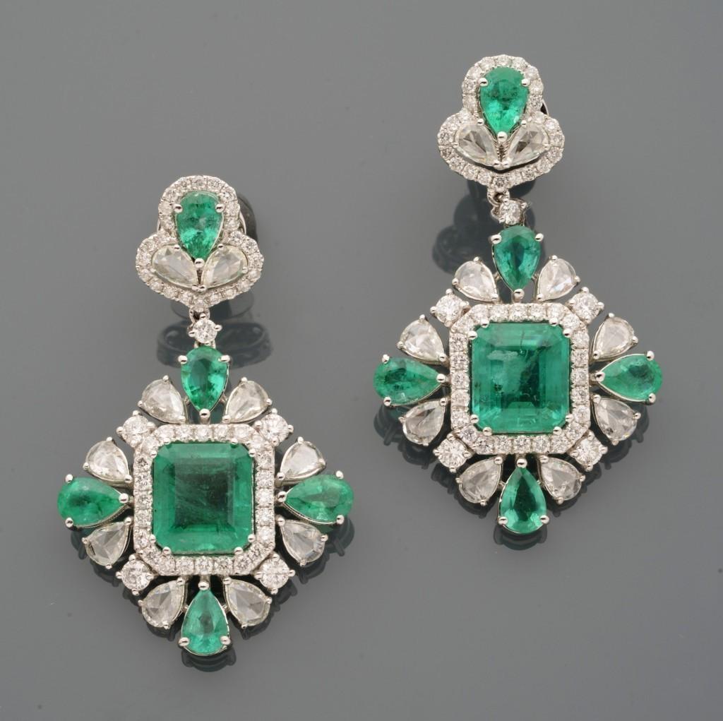 Pendants d'oreilles en or gris, chacun dessinant un motif rayonnant alterné d'émeraudes et de diamants ronds et poires, centré d'une émeraude rectangulaire plus importante