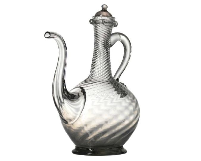 Hurdal. Svagt gråaktigt glas. Sfärisk form med sneda spår och lång hals med rullande mynningsring och handtag och pip. Ca. 1790. Blomqvist.