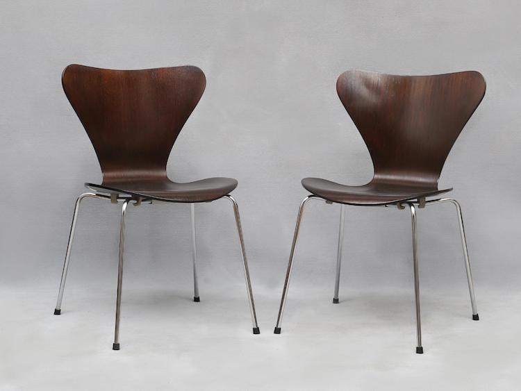 """Stolar 1 par """"Sjuan"""". Arne Jacobsen för Fritz Hansen, mörkbetsad ek, benställning av förkromat stålrör, tillverkade 1974 (en sits med smärre fläckar). Utrop: 1,500 SEK."""