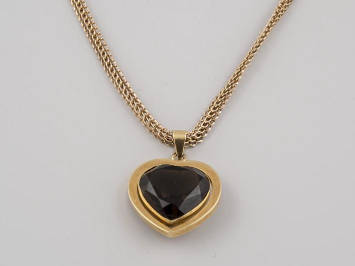 Collar con colgante de oro decorado con una piedra de color en talla corazón