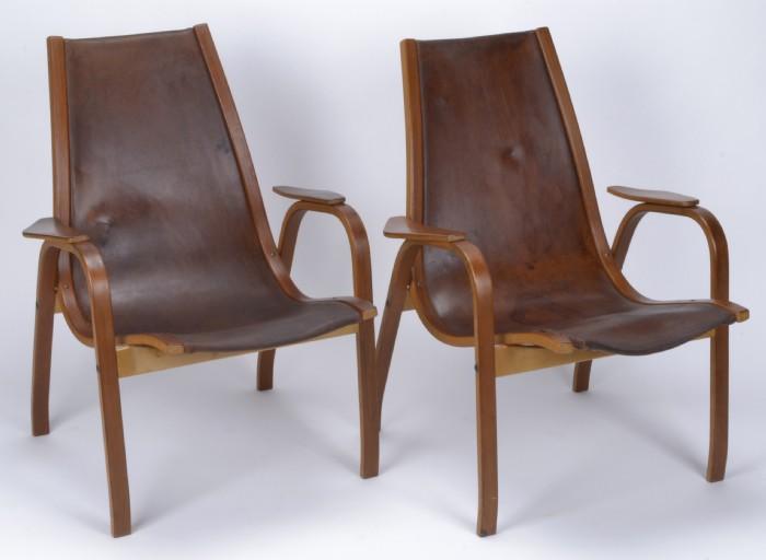 Armlänsstolar, ett par - Yngve Ekström 'Kurva'. Stomme av bland annat teak. Klädsel av brunt läder. Märkta YE. Höjd 84 cm. Skador och slitage.
