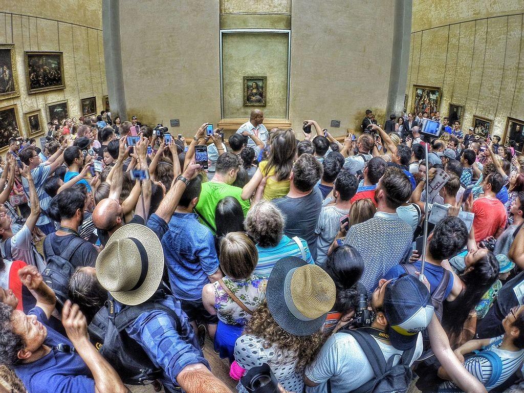 Des visiteurs se pressant devant la Joconde de Léonard de Vinci Image via Wikipédia